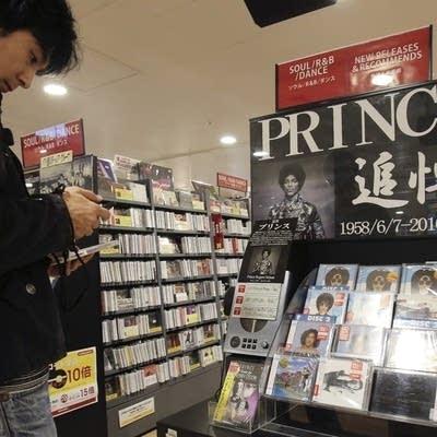 E9172a 20160425 a customer looks at a cd of princes music
