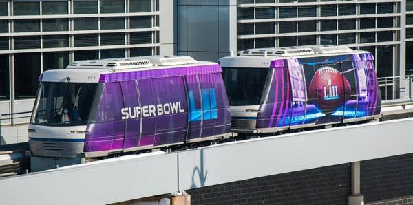 An airport tram advertising the Super Bowl.