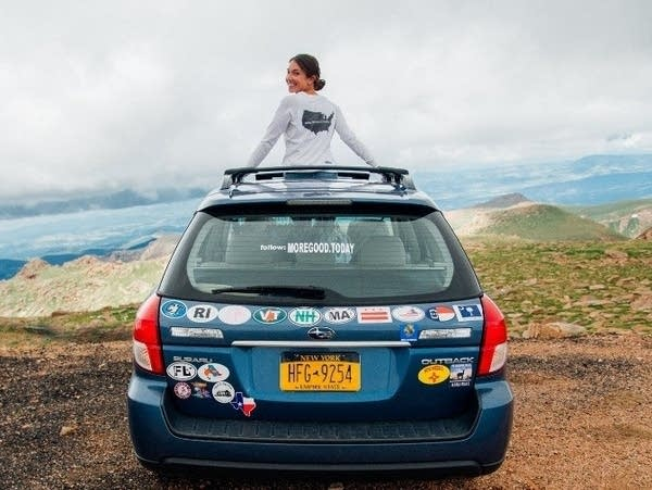 Mary Latham and the Blue Subaru she's driving across the country