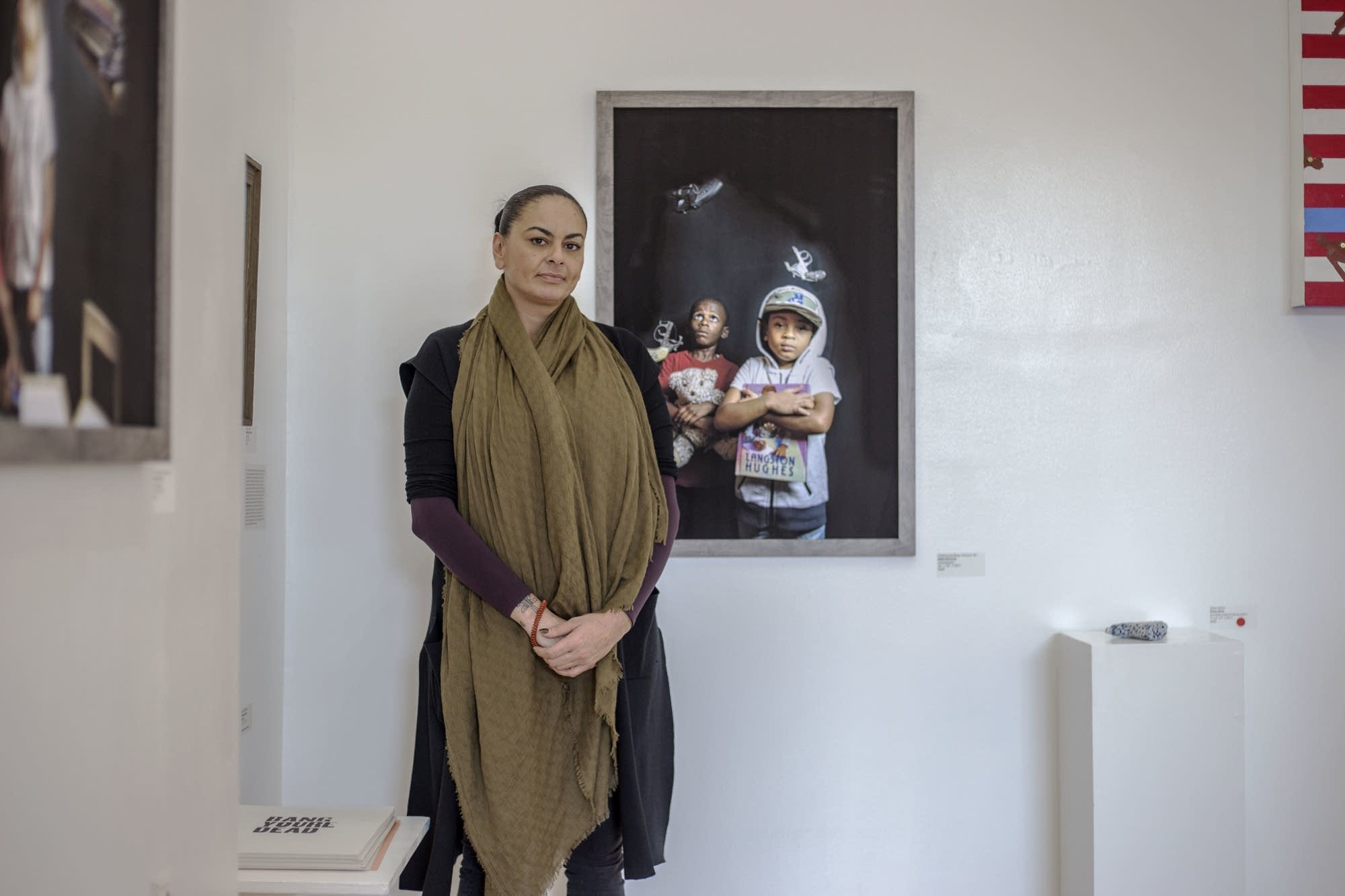 Nikki McComb poses next to her work at Gamut Gallery.