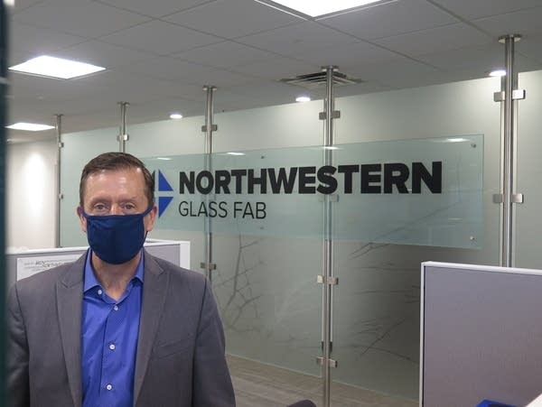 A man with a face mask stands in an office space.