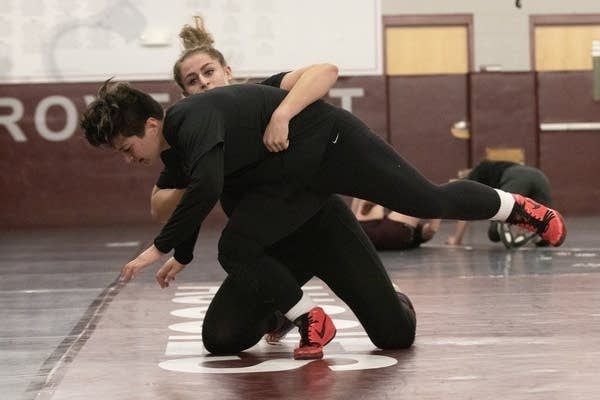 Two people wrestling on a mat in a gym.