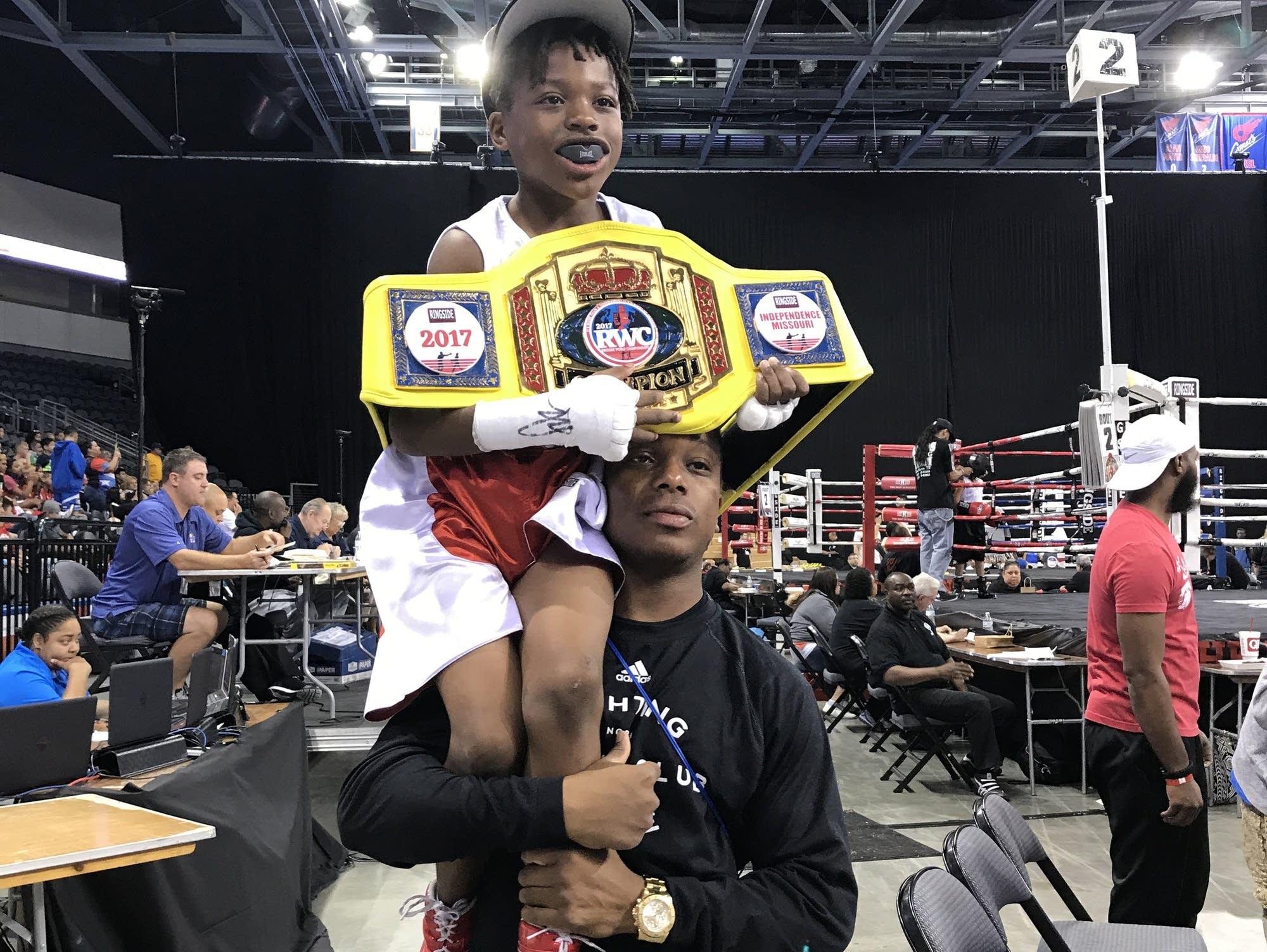 Morgan McDonald, Jr., is held up by his father after winning.