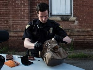 A police officer searches the purse of a suspected sex worker