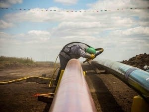 Here, a worker lays down pipeline in North Dakota.