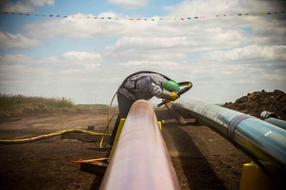 Here, a worker lays down pipeline in North Dakota.