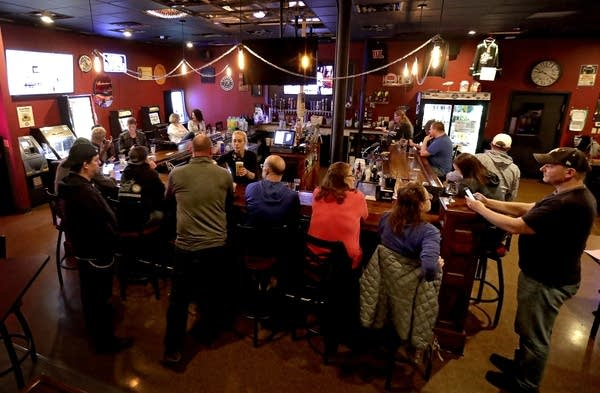 People gather at a bar.