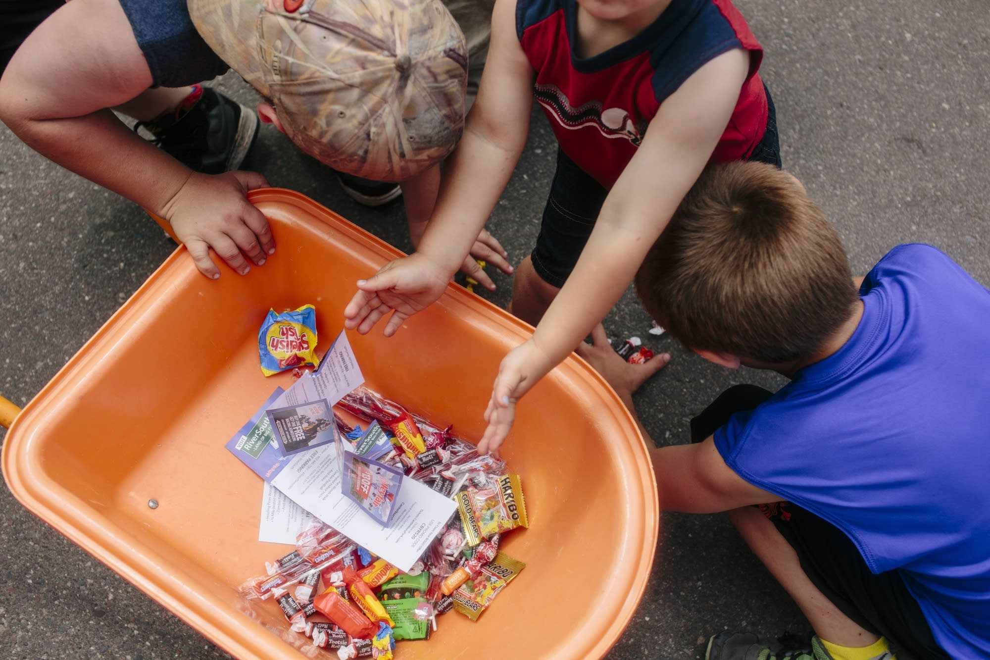 Kids load candy into a miniature wheelbarrow.