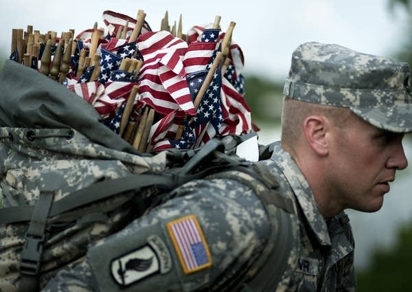 A soldier carries flags in Arlington
