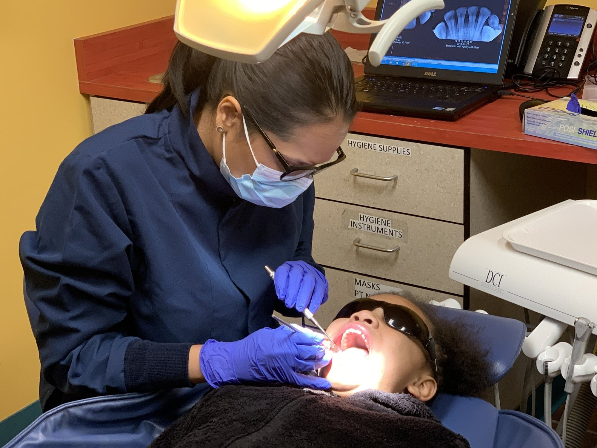 Dr. Megha Agrawal examines the teeth of 9-year-old Lanajah Chase