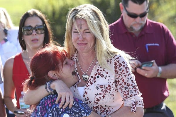 Parents wait for news after a reports of a shooting in Parkland, Fla.