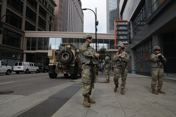 Armed soldiers stand on a city street.