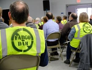 Opponents of the Fargo Moorhead diversion project wear construction vests.