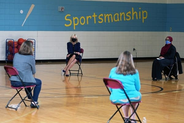 Jill Biden takes part in a forum with educators in a school gym.