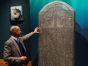 Franck Goddio points out a detail in the Stele of Thonis-Heracleion.