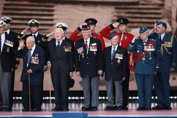 Veterans salute from the stage as they attend the D-Day commemorations.