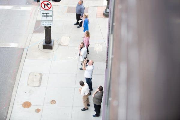 Pedestrians gather on 7th Street in St. Paul, Minn. to watch a raccoon.