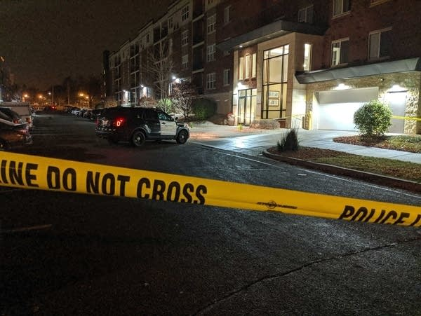 Police tape blocks the view, with a police car in front of an apartment.