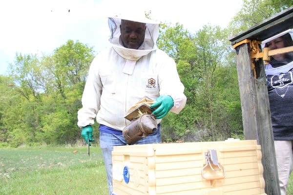 A man aproaches his bee hive body