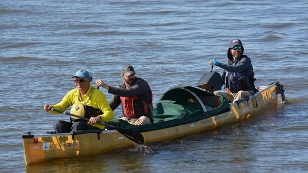A team paddles in a canoe on the river.