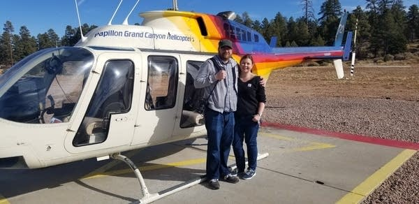 A couple (Andrew and Genevieve) stand in front of a tourism helicopter