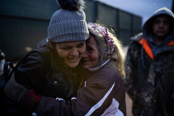 Volunteer Renee Avery hugs camp resident Kat Yanez.