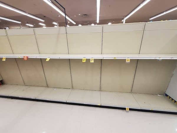 Empty shelves where the paper towels should be in the grocery store