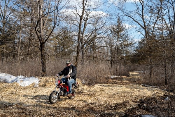 Tommy Reuter rides the wood chip path through the woods with his dog McCoy.