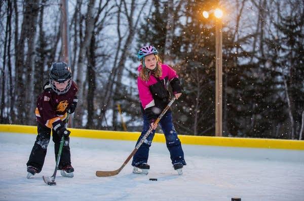 Two children play hockey.