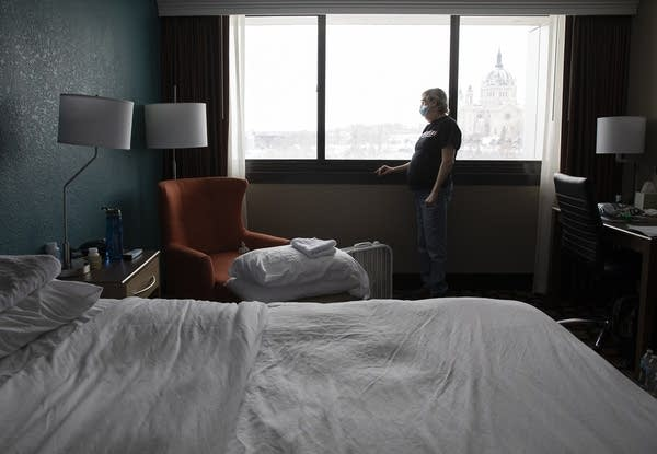 A woman stands near a window in a hotel room.