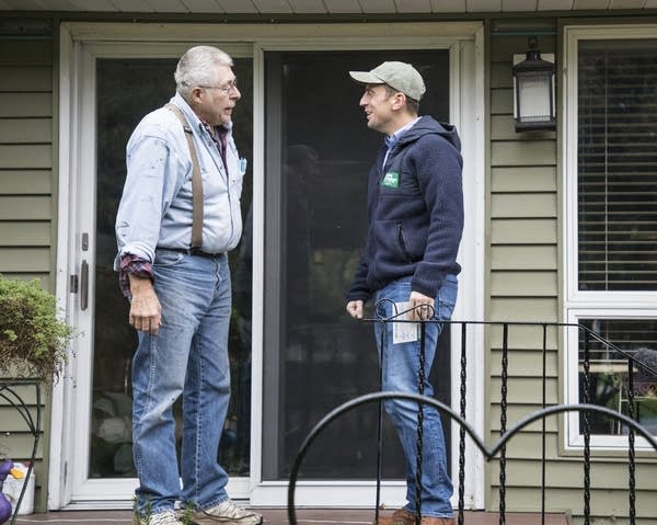 Dan Feehan, right, chats with Austin resident Jerry Adams.