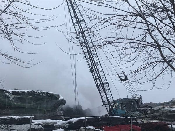 Smoke rises from a vehicle scrapyard