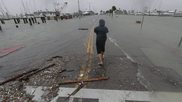 A man takes photos of a road beginning to flood