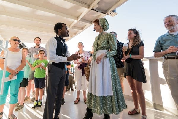 Two actors talk on the boat deck as audience members stand around them.