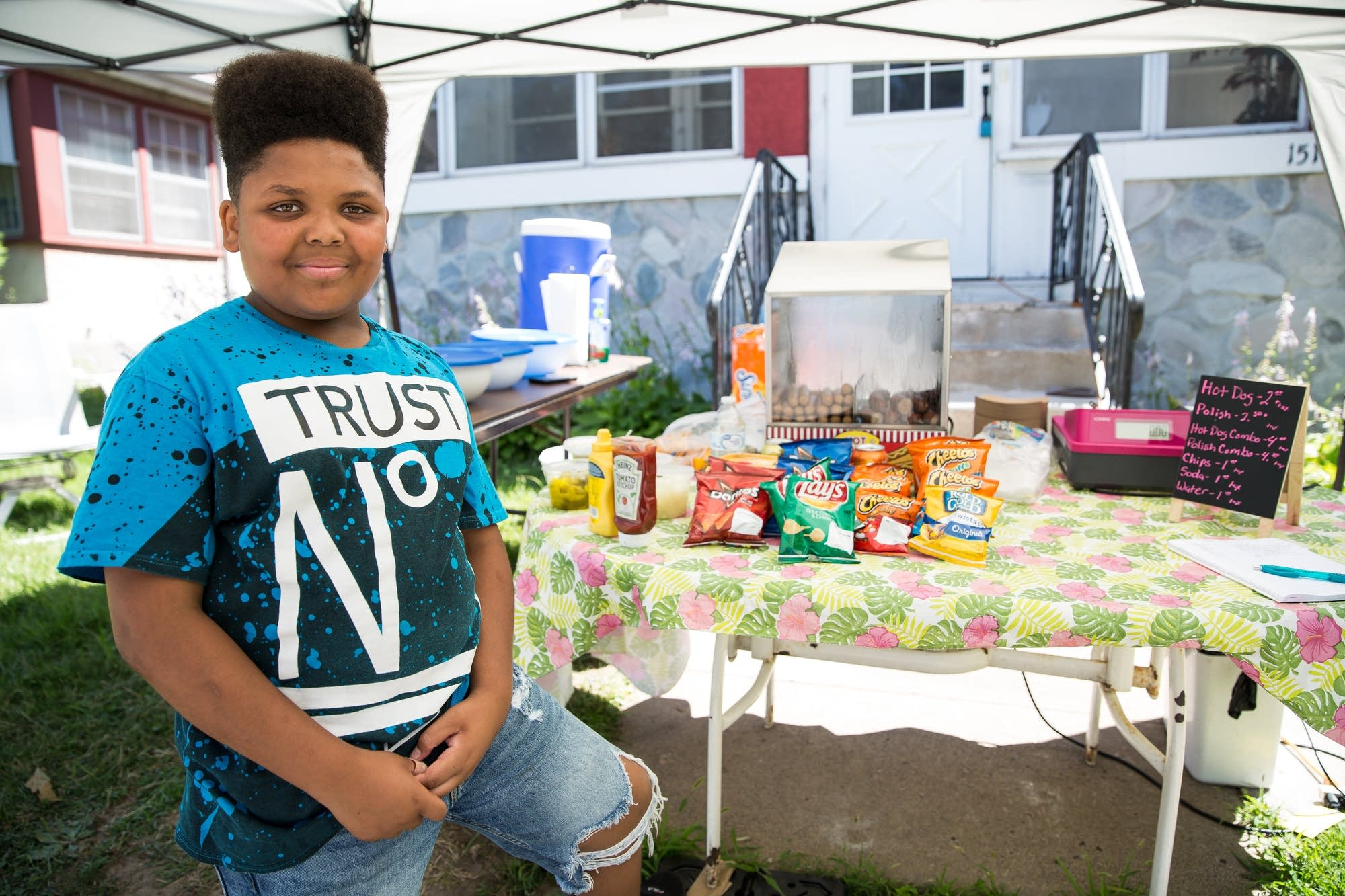 Jaequan Faulkner, 13, stands for a portrait in front of his hot dog stand.