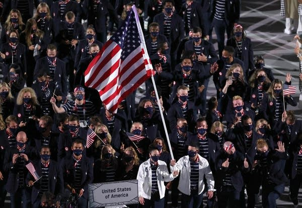 Two U.S. flag bearers lead their team during the Olympics.