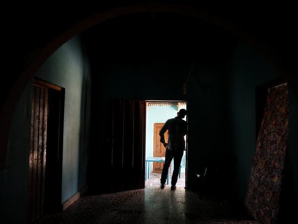 A Honduran father stands in a doorway in his home