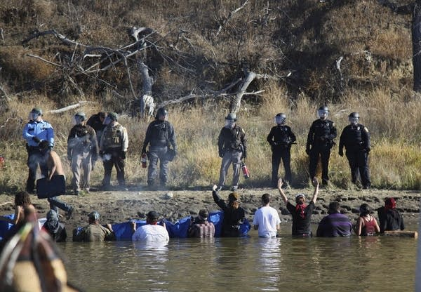 Protesters wade in a creek to demonstrate.