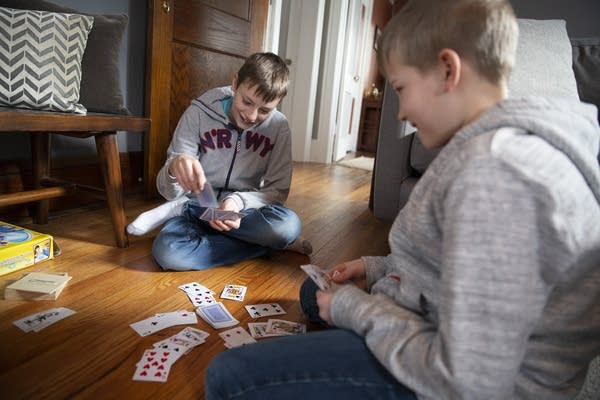 Reed and Brennan Schumann play a card game during a day off from school.