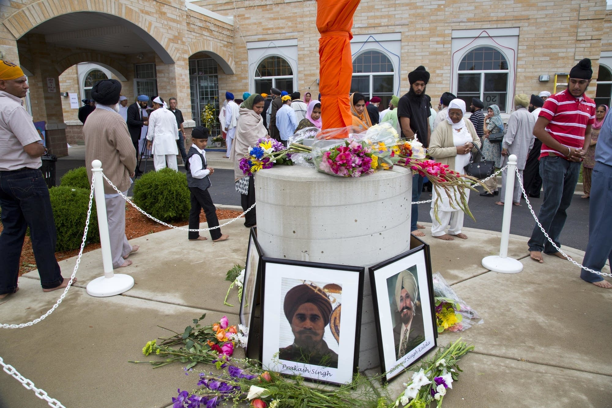 People walk around a flag pole outside the Sikh Temple of Wisconsin.