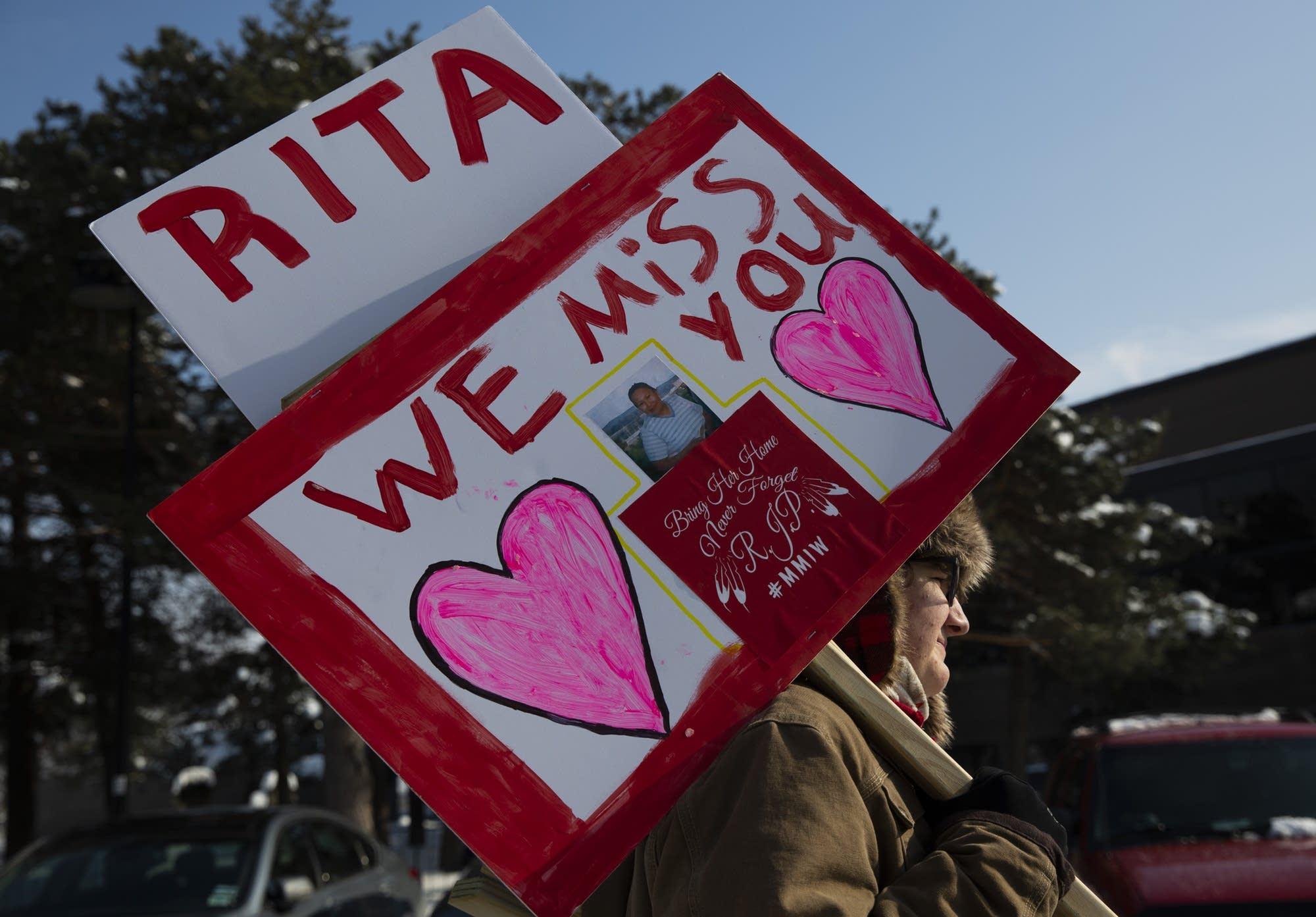 Thomas Peters of Tama, Iowa carries a sign honoring Rita Papakee.
