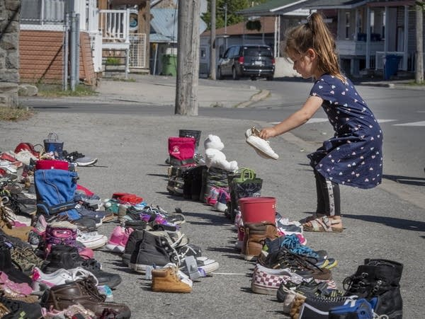 A girl places a pair of shoes on a memorial