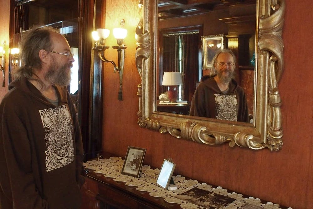 Charlie Parr smiles at himself in a mirror