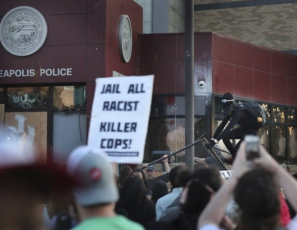 A protester climbs over a fence to the Minneapolis police 3rd Precinct