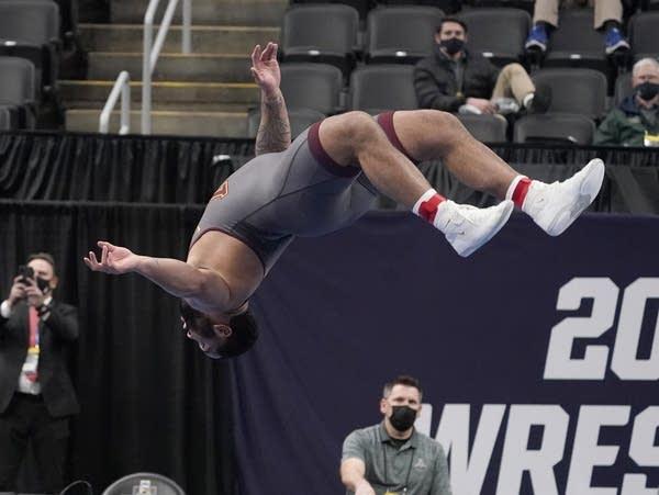 A wrestler does a backflip after winning a match