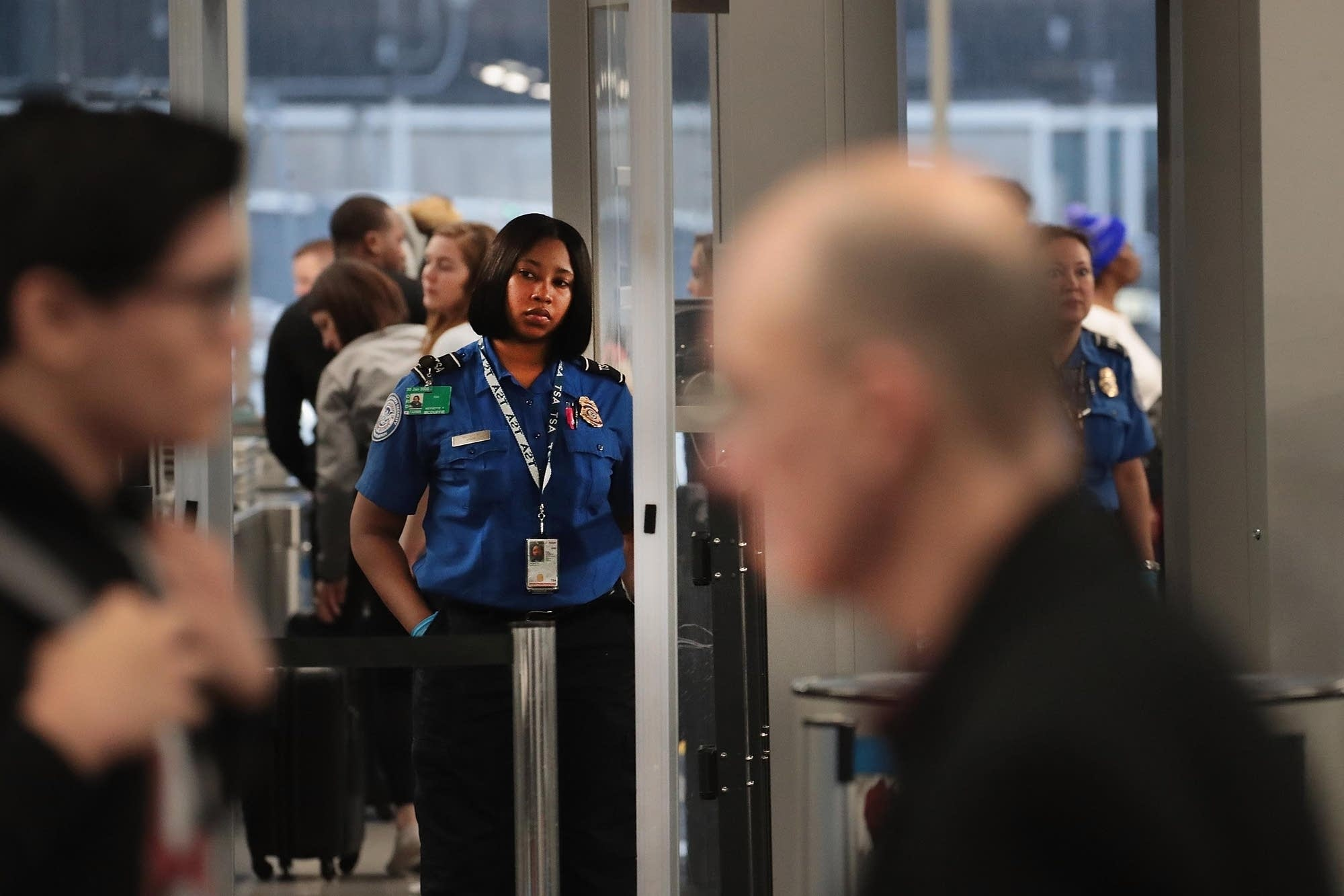 A TSA worker screens passengers and airport employees in Chicago.