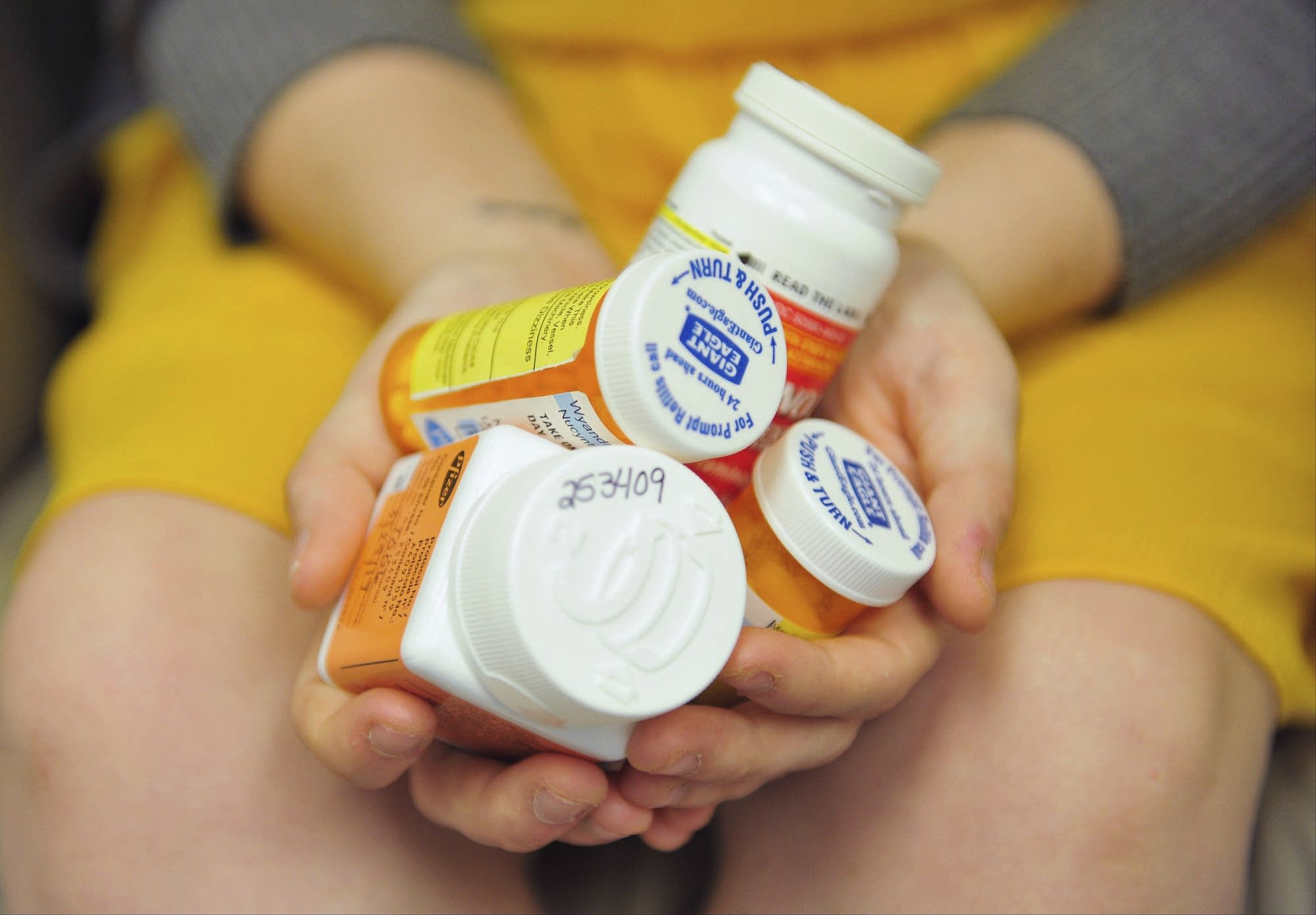 Heidi Wyandt, 27, holds a handful of her medication bottles