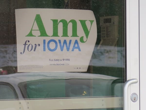 A sign that says Amy for Iowa in a window