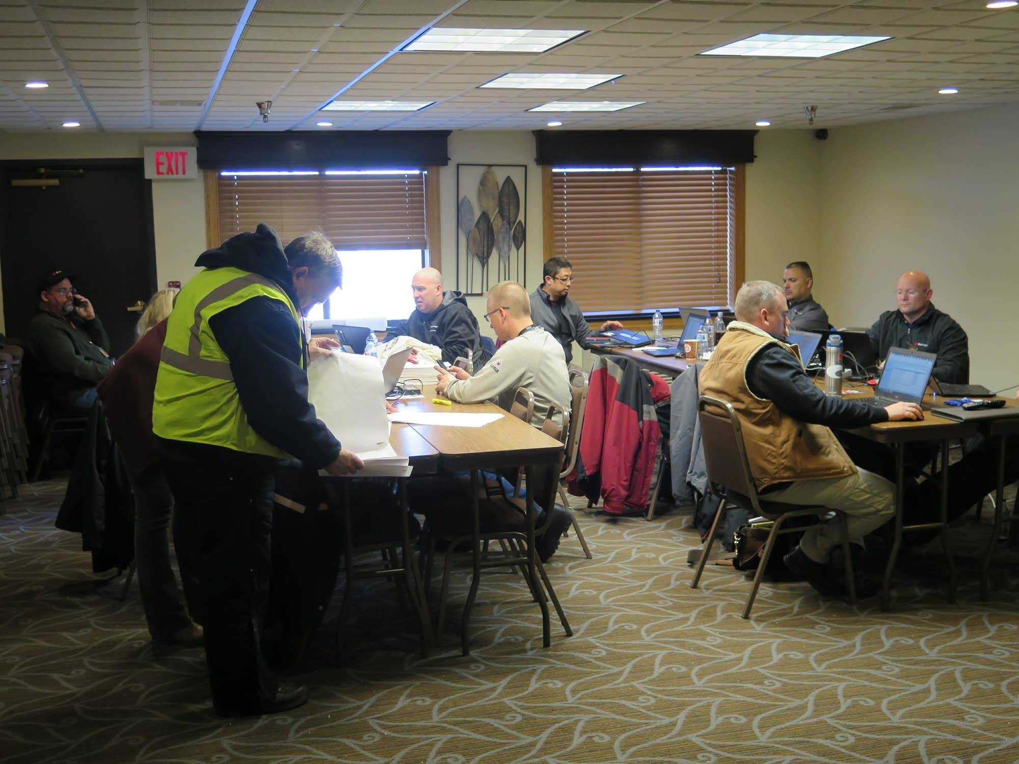 Employees work out of a conference room at the AmericInn.