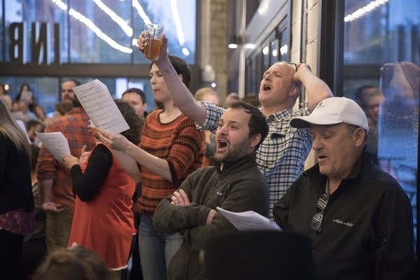 People sing along with beer-related choir numbers.